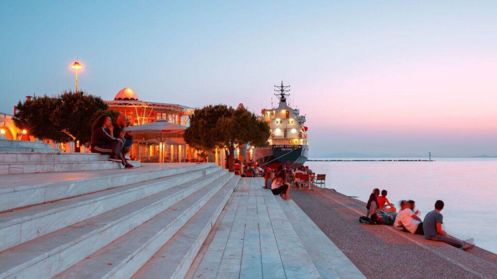 Patras limanına yakın bir bölgede gençler gün batımını izliyorlar.
